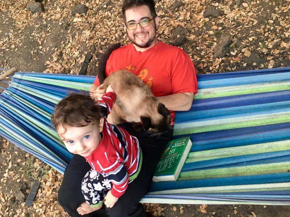 [background photo of Dani, a white genderqueer with short hair and a trimmed beard, beaming, in a blue and green hammock with a siamese cat, an adorable toddler, and a Sophie Kinsella book called My Perfect Life. This was not posed, it's just a great book I happened to be re-reading.]